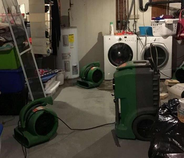 SERVPRO equipment drying up the remainder of the water from the leak in the basement.