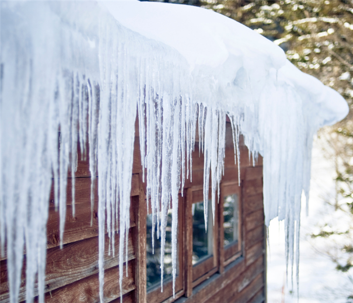 photo of ice dam forming on the edge of roof of log cabin, large icicles hanging down
