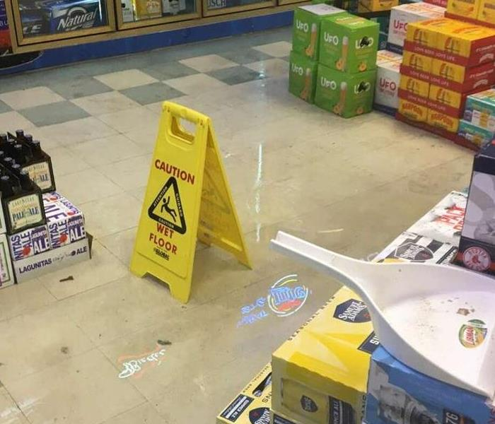 Water on floor of a liquor store with cases of beer stacked around the water with a beer cooler seen in the background